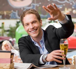 man in bar waving to attract attention