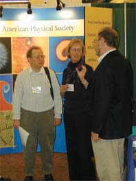 Standing in front of the spectacular APS booth at the January meeting of the American Association of Physics Teachers in Austin, Texas, Kim Bess (center), Director of Science and Educational Technology at the San Diego City Schools, explains the virtues of teaching physics first (i.e. before chemistry and biology). Listening raptly are Kevin Aylesworth (left) and Fred Stein of the APS Department of Education and Outreach.