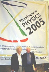 "Two Nobel laureates, Albert Einstein (left, as portrayed by Marc Spiegel) and Leon Lederman (right, playing himself) stand in front of a gigantic World Year of Physics banner at the ""Just Physics"" reception for physics teachers at the meeting of the National Science Teachers Association in Dallas in early April. The reception was sponsored by PASCO, as well as by the American Association of Physics Teachers and the World Year of Physics 2005. Photo Credit: Jessica Clark"
