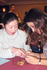 Lily Min (l) and Su Lin Haggerty, two physics teachers in the LA area, disassemble a small DC motor in a workshop at the APS High School Physics Teachers' Day. This Teachers' Day was partially supported by Lucent Technologies and Applied Materials. Photo Credit: Edward Lee