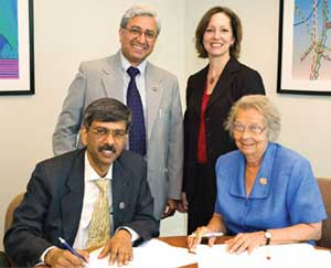 Signing the memorandum of understanding are IUSSTF Executive Director Arabinda Mitra (left) and APS Executive Officer Judy Franz (right). Standing guard are Kamal Kant Dwivedi (left),