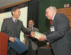 Chenggang Xu (left) presents APS President Arthur Bienenstock (right) with a copy of the three-volume Chinese translation of Einstein's collected works
