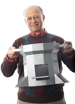 Ashok Gadgil holding a stove that improves energy efficiency