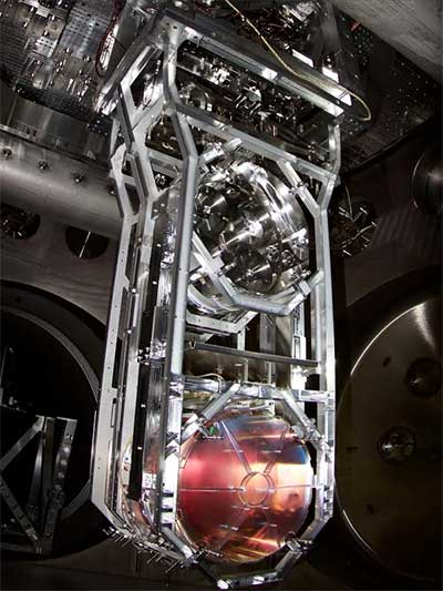 The photo shows one of LIGO's mirrors, which reflect the laser beams along the lengths of the detector arms. The 40 kg mirror is suspended below the metal mass above by 4 silica glass fibers.